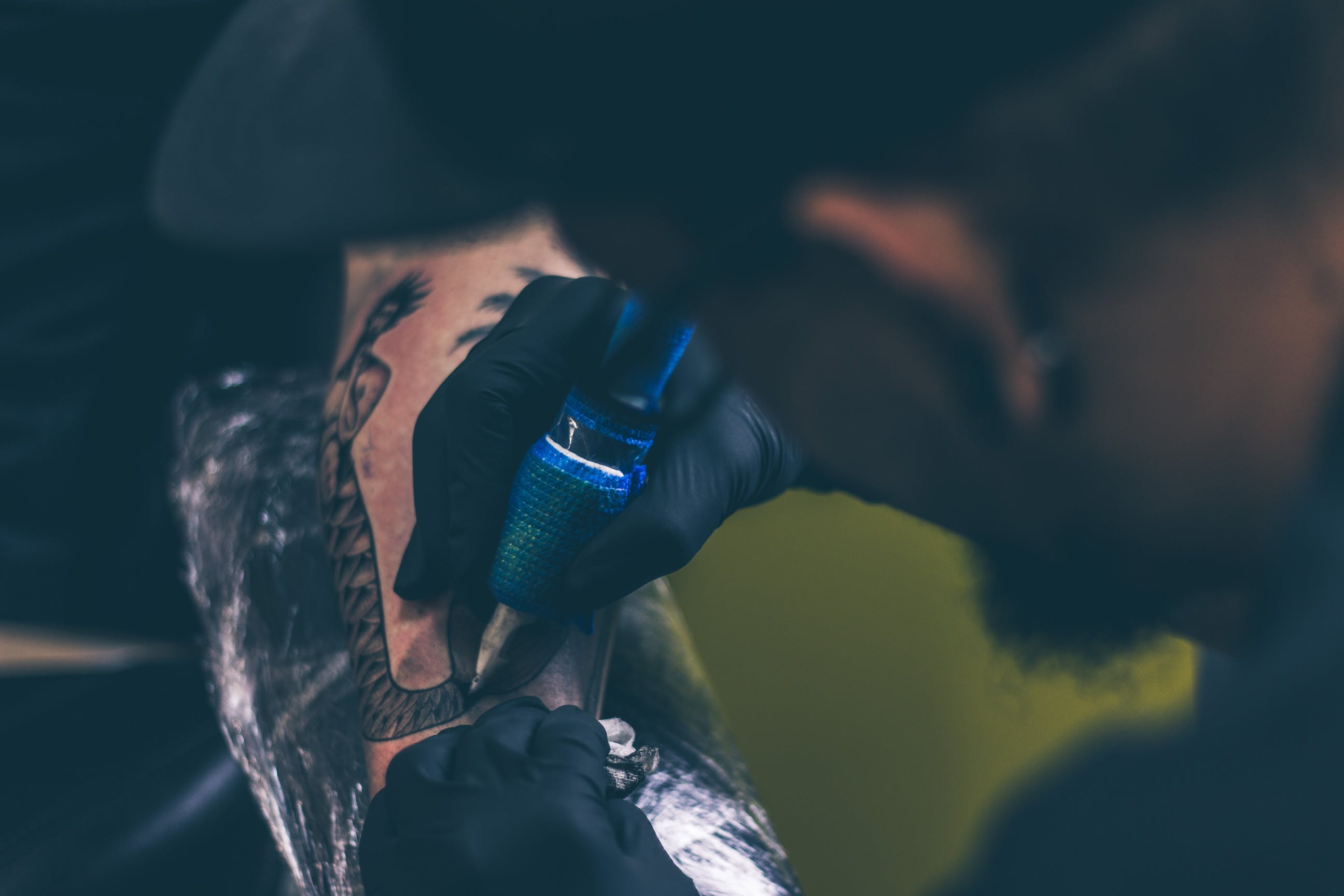 Man Tattooing Person on Arm