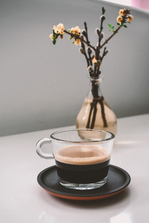 Vase with blossoming willow stem composed with coffee cup