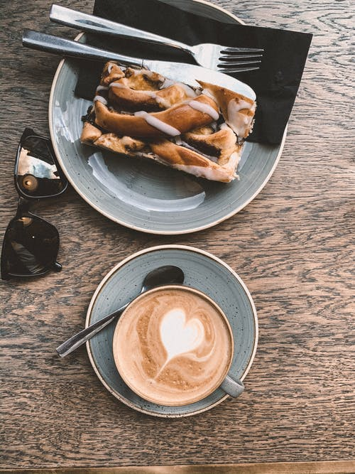 Top view sunglasses and cup of coffee with heart shaped latte art served on wooden table in cafe with plate of delicious sweet pie topped with chocolate syrup