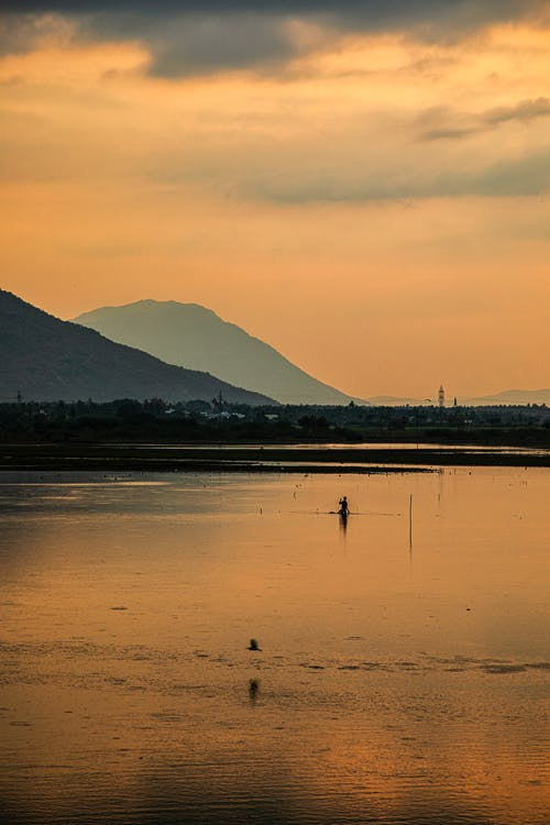 Silhouette of unrecognizable person fishing in calm lake surrounded by mountains during sunset