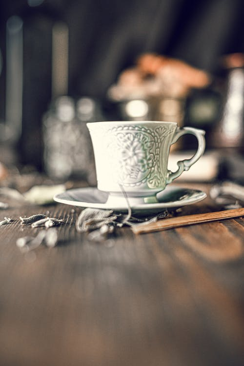 Old fashioned carved porcelain cup of coffee with saucer served on wooden table during breakfast