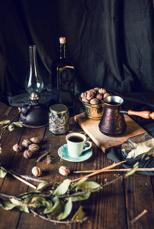 Coffee cup and pot with walnuts bowl placed on table with various spices and retro decorations