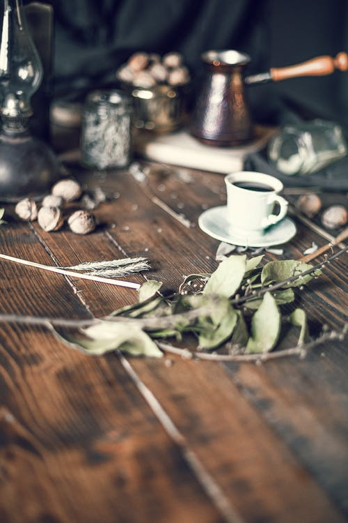Coffee cup and dried leaves on wooden table