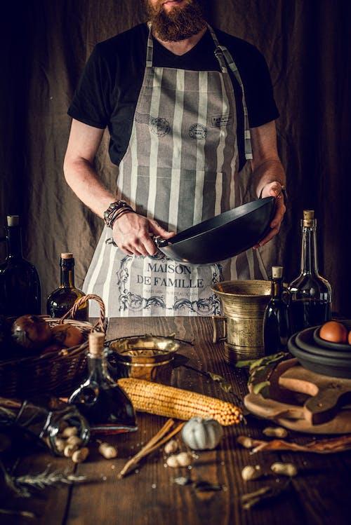 Crop cook preparing healthy rustic food at wooden table