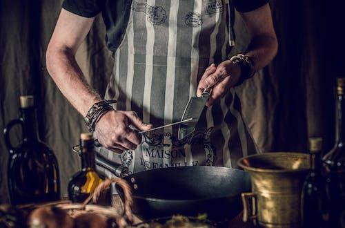 Crop faceless chef sharpening knives before preparing food in frying pan