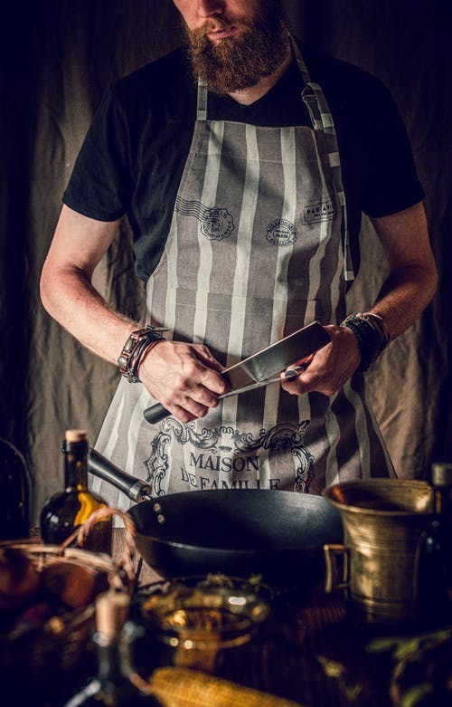 Crop bearded male chef sharpening knife in kitchen