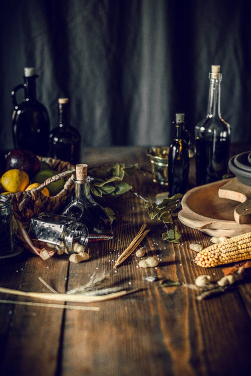 From above of bottles with assorted oil and vinegar placed on wooden table in kitchen near fruit basket composed with corn and herbs