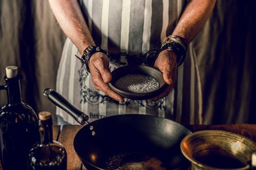 Crop cook adding spices into pan in kitchen