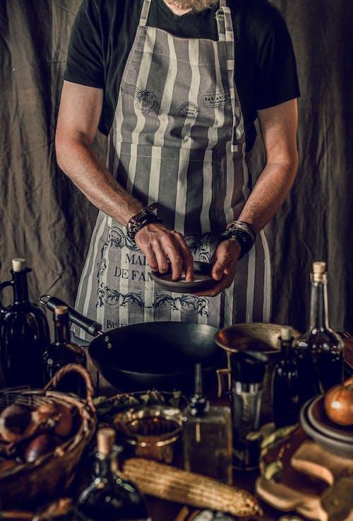 Faceless male chef adding kosher salt while cooking dinner