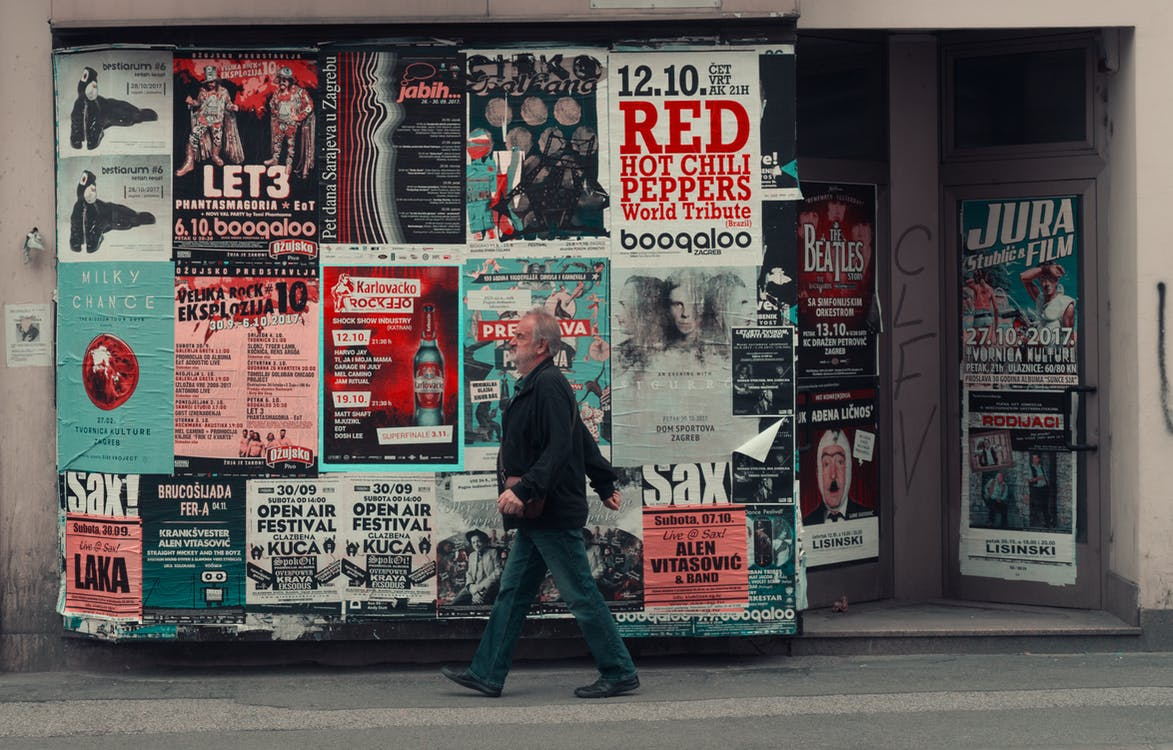 Side view of senior man in casual clothes walking along wall of modern building with posters while having stroll on city street