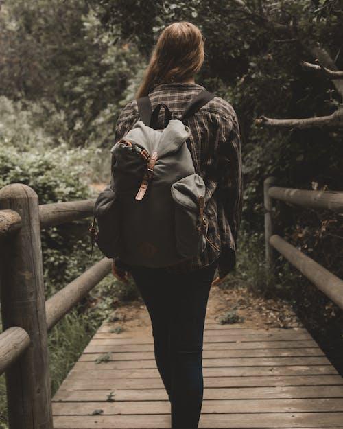 Woman Walking on Bridge Carrying Backpac