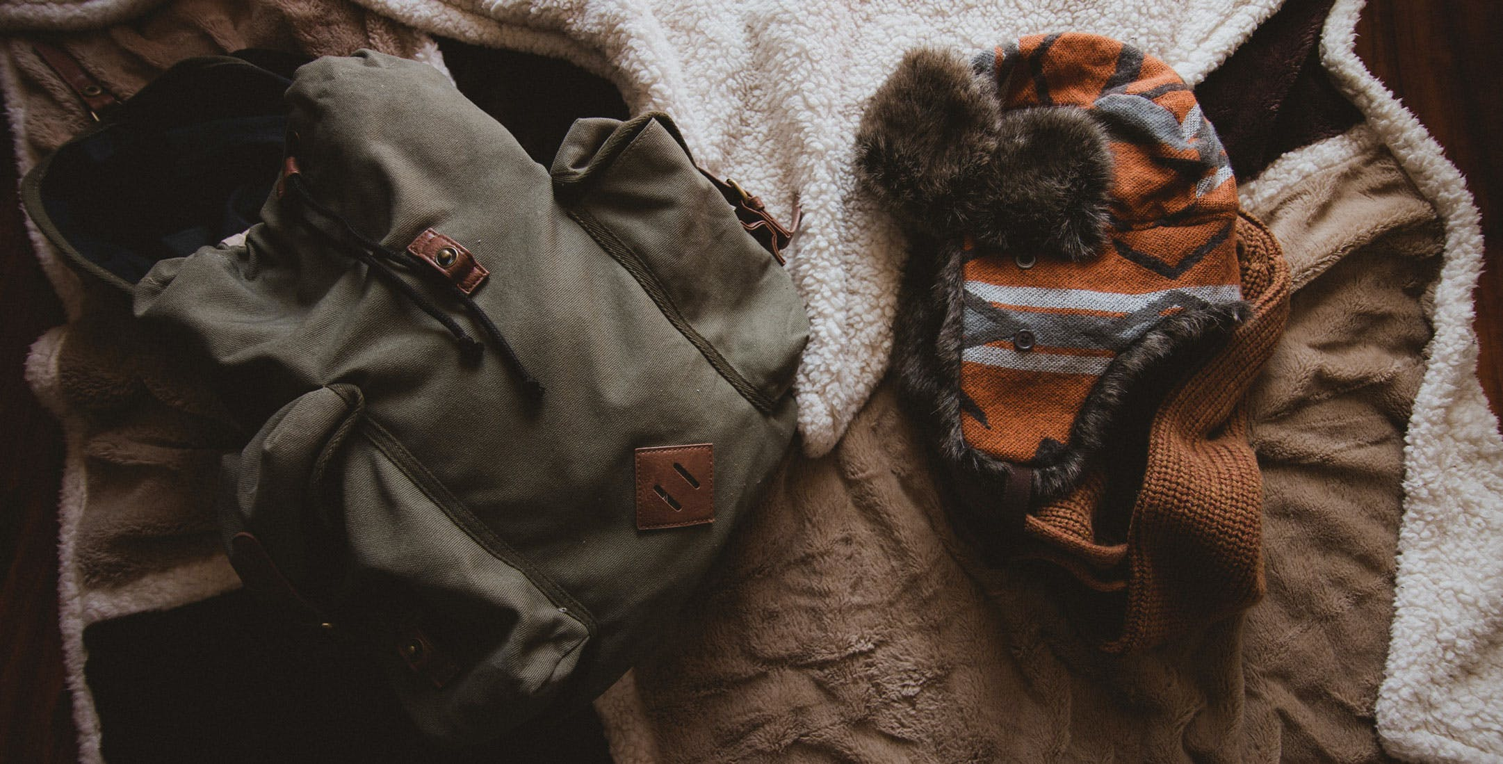 Gray Backpack Beside Orange Knit Hat