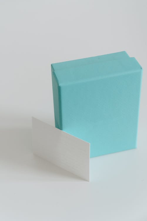 Small present box with blank business card on white background