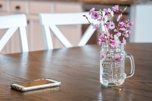 Cut glass vase with fragile pink cherry tree lowers and modern mobile phone placed on wooden table in light dining room
