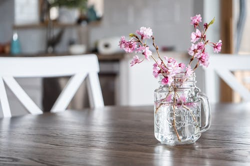 Vase with blossoming cherry tree branches on table