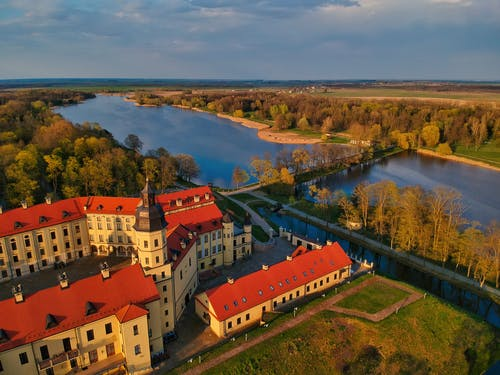 Drone view scenery of beige Nesvizh Castle with brown tiled roofs located on green riverside in Belarus