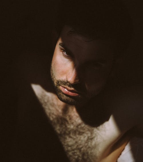 From above adult shirtless man with beard and chest hair looking away in darkness illuminated with sun ray