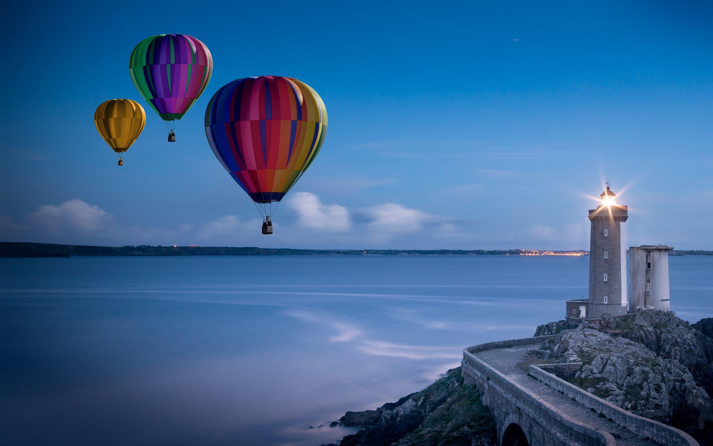Three Flying Hot Air Balloons Near Lighthouse