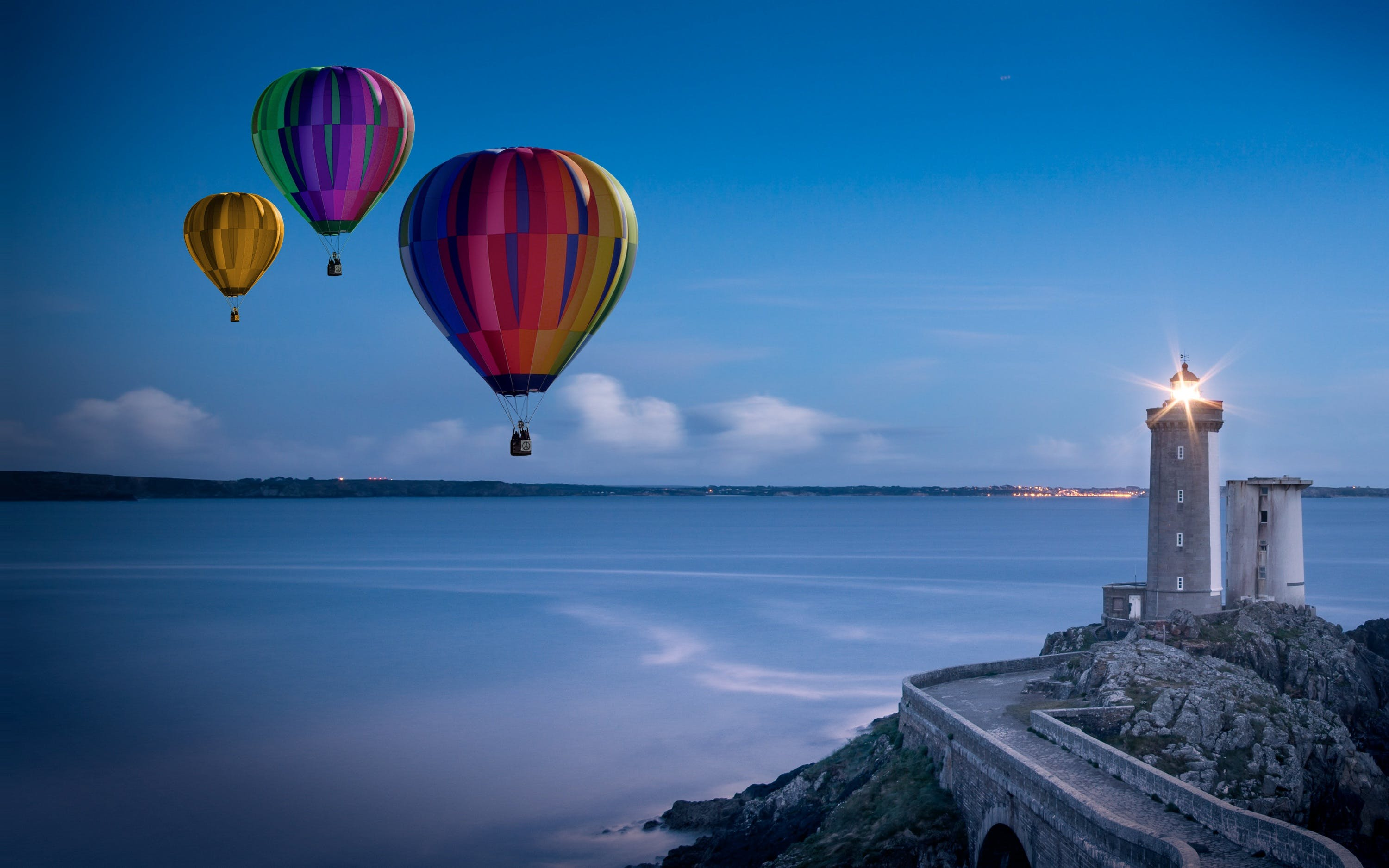 Three Flying Hot Air Balloons Near Lighthouse
