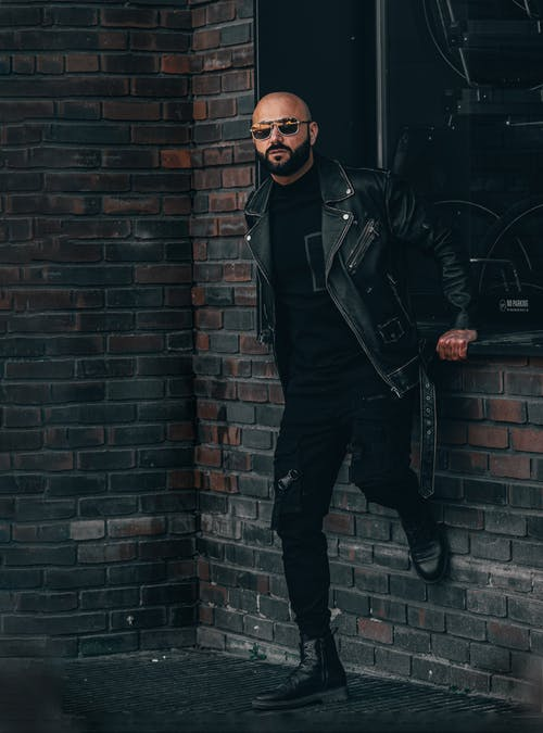 Man in Black Leather Jacket Standing Beside Brick Wall