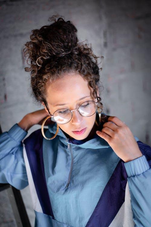 Modern curly woman in sportive jacket