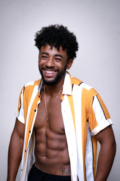 Laughing muscular black man at white wall