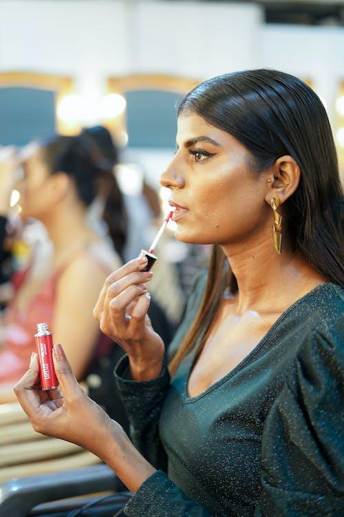Trendy ethnic model applying lip gloss in dressing room