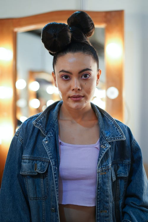 Trendy ethnic woman with bow hairstyle in denim jacket