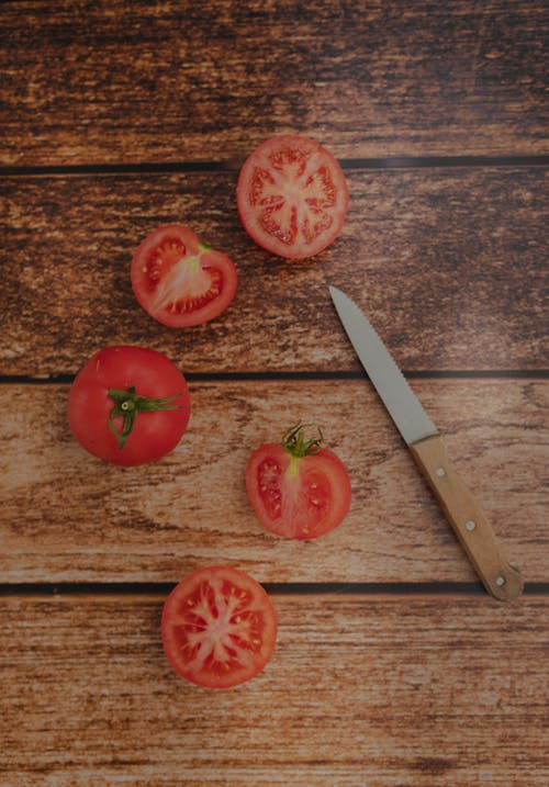 Fresh cut tomatoes and knife on wooden table