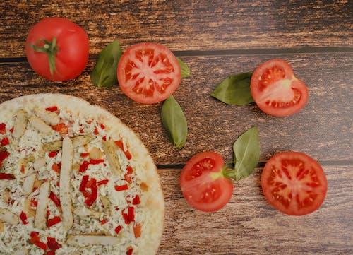Delicious pizza with chicken near ripe tomatoes