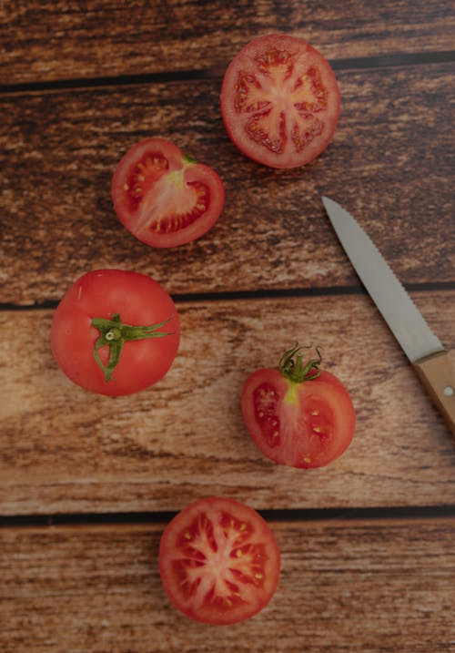 Halves of ripe tomatoes with knife on table