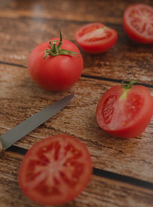 From above of halves of bright fresh juicy tomatoes near sharp knife on rustic style table at home