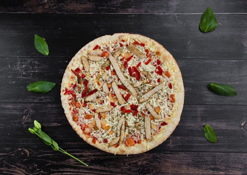 Tasty pizza with chicken near fresh basil leaves