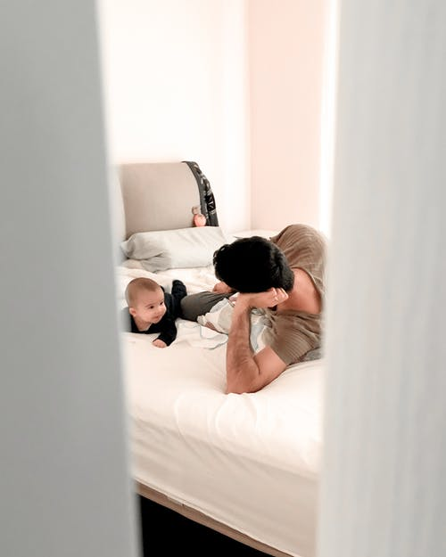 Anonymous father looking after baby on bed in apartment