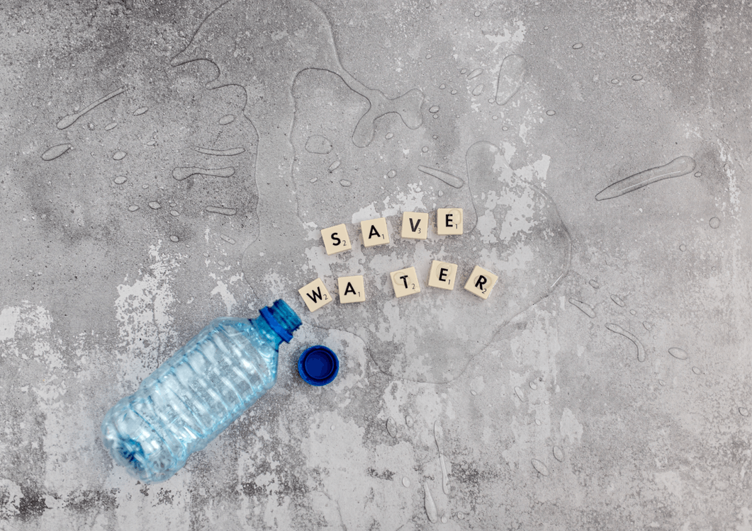 Cubes with letters and plastic bottle with spilled water