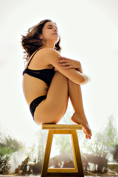 Alluring peaceful female in underwear sitting on chair