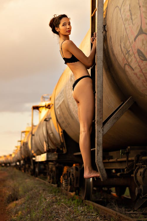Slim woman in underwear standing on tank wagon stairs