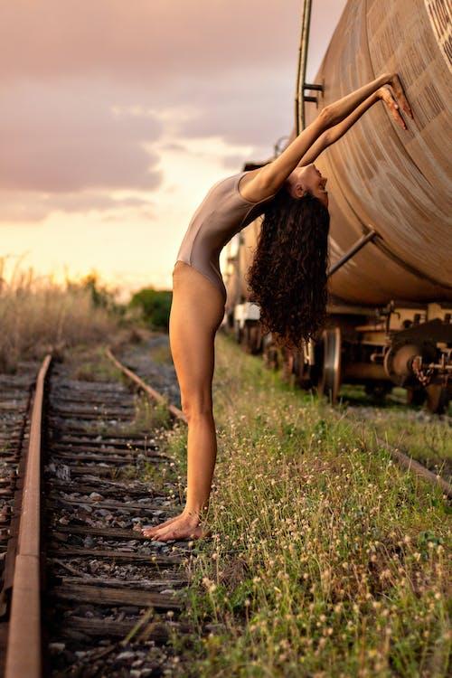 Flexible woman in bodysuit leaning on tank car on railroad