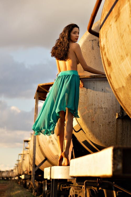 Topless woman standing on tank car in railroad