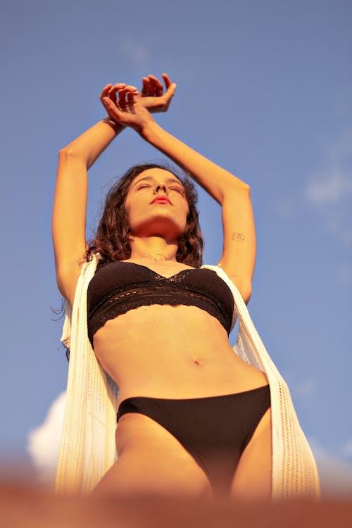Sensual woman in underwear raising arms towards blue sky