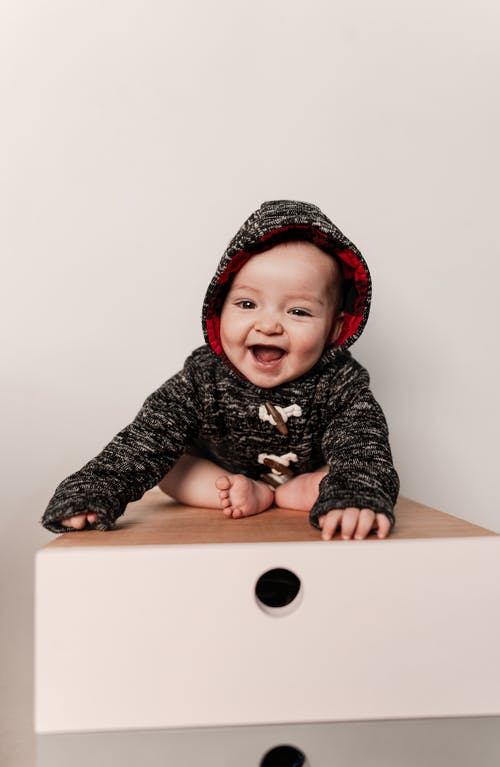 Full body laughing adorable toddler in cozy sweater with hood sitting on drawer and looking at camera