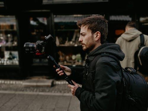 Focused male photographer recording video on photo camera on street