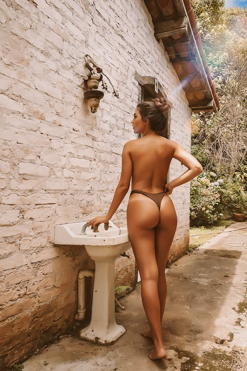 Back view full body seductive topless female in bikini standing with hand on waist near washbasin outside rural brick building