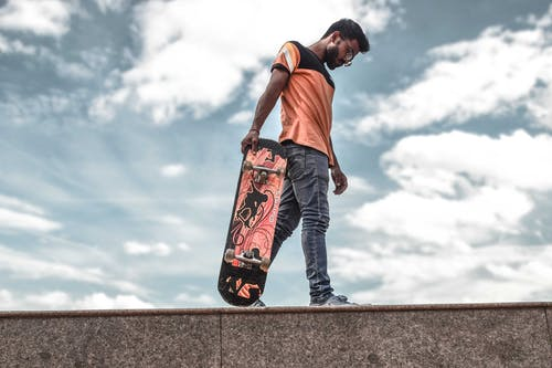 Focused young ethnic man with longboard on street