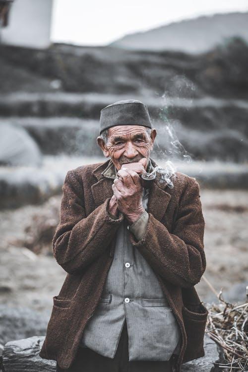Thoughtful elderly ethnic man smoking pipe in countryside