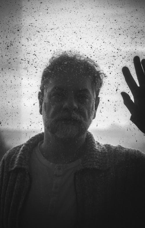 Mature man behind glass covered with water drops