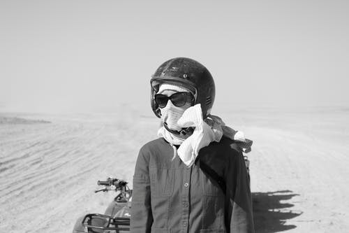 Black and white anonymous biker in helmet covering face with scarf and sunglasses standing near motorbike on sandy terrain