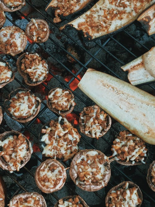 Top view appetizing stuffed mushrooms and ripe cut eggplants roasting on barbecue grid