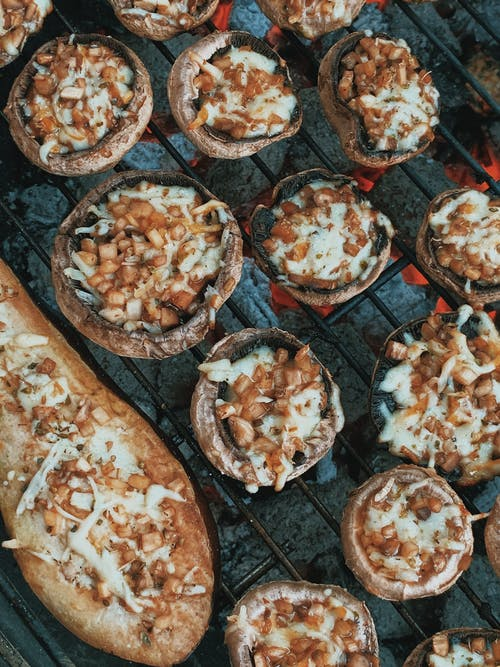 From above delicious homemade stuffed mushrooms and eggplant under layer of cheese roasting on barbecue grill
