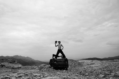 Black and white of anonymous shirtless male standing on ruined car on rough rocky ground against cloudy sky